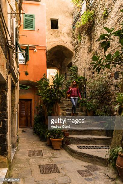 Typical ligurian alley in Vernazza. A girl walking down a staircase. Cinque Terre, La Spezia, Liguria