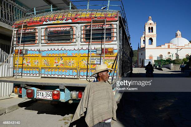 A typical man wearing a sombrero stands in front of a Chiva bus in the town center near the market place on January 13 2015 in Silvia Colombia The...