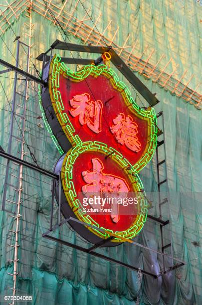 A typical neon sign advertising a pawn shop hanging opposite a highrise building covered in bamboo scaffolding and green netting in the workingclass...