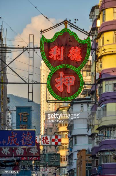 A typical neon sign advertising a pawn shop provides a perch for a flock of small birds in Sham Shui Po Hong Kong