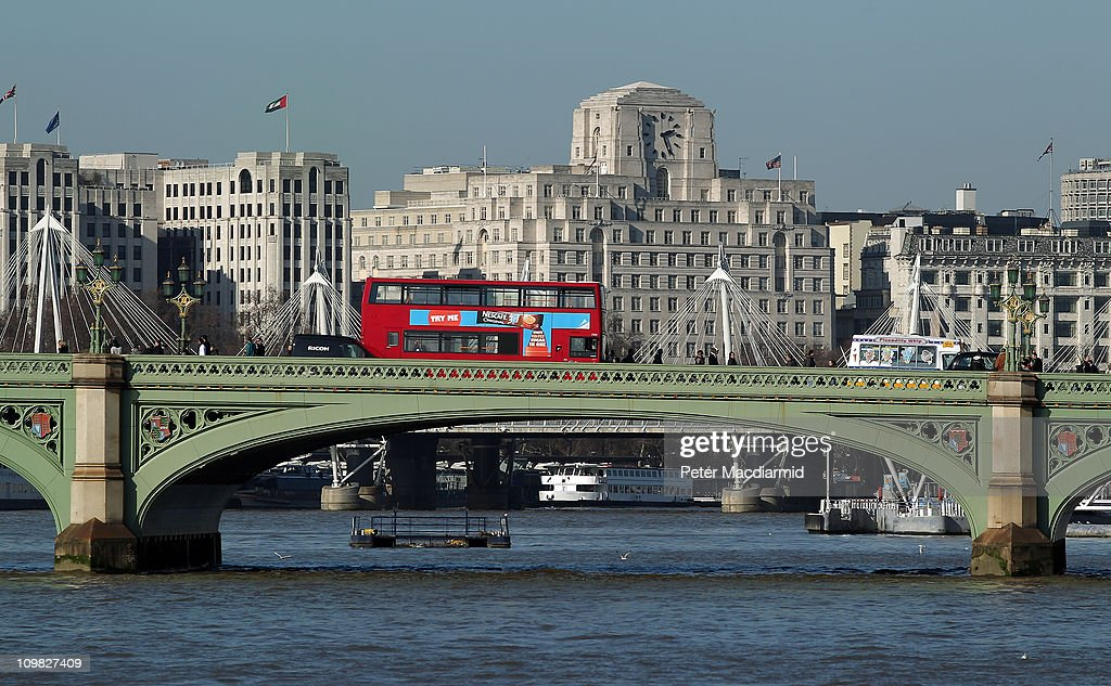 A typical red bus travels over Westminster Bridge over The River Thames on March 7, 2011 in London, England.