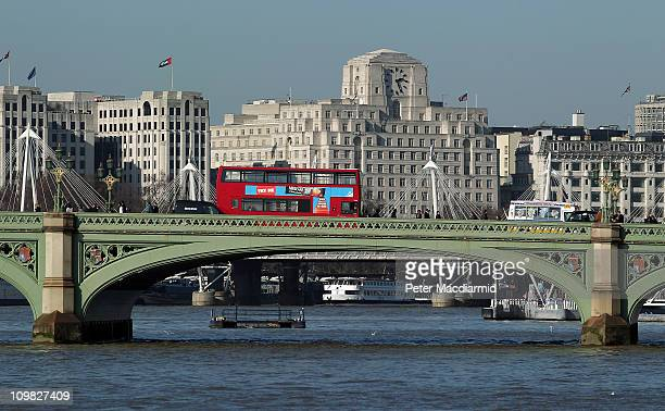A typical red bus travels over Westminster Bridge over The River Thames on March 7 2011 in London England