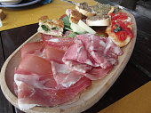 Typical rustic tuscan appetizer with crostini, prosciutto, brawn, salami, cheese on a wooden tray . Italian starter