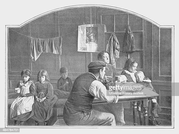 Typical scene in an early twentieth century London slum with parents and five children living in a single room