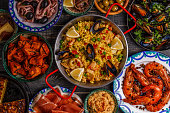 Typical spanish tapas concept. Concept include slices jamon, bowls with olives,  anchovies, spicy potatoes, mashed chickpeas, shrimp, calamari, manchego with quince marmalade, pans with tortilla, pael
