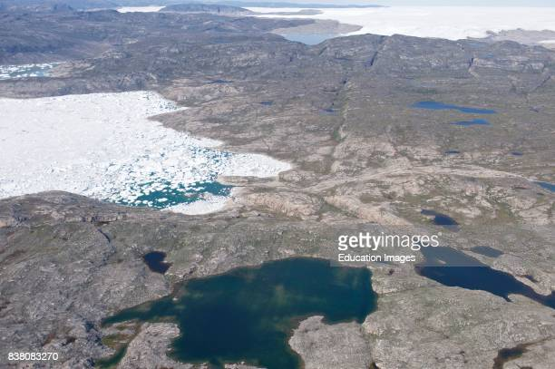 A typical view of the Greenlandic landscape photographed a couple of hundred meters above the ground Here we see melt water lakes in the foreground a...