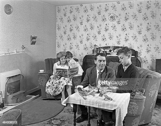 Typical working class living room scene with family 11 July 1962 In a typical living room scene from the early 60s a father helps his son with the...