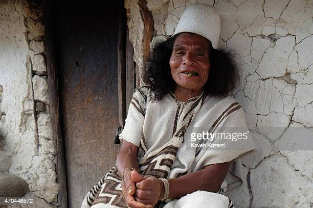 A typically dressed Arhuaco man chews Coca leaves while sat in front of a hut in the walled village on January 23 2015 Nabusimake Colombia Nabusimake...