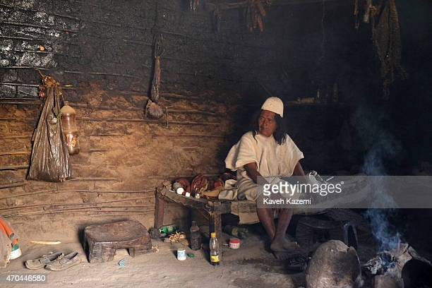 A typically dressed Arhuaco man one of the community chiefs sits in his hut with smoke rising from a log fire inside the room on January 23 2015 in...
