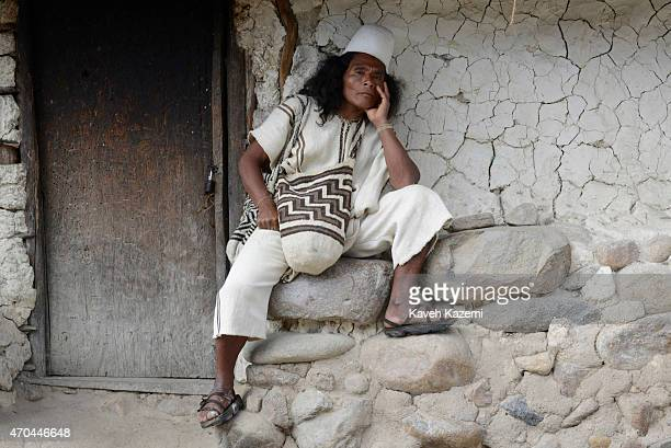 A typically dressed Arhuaco man sits outside a hut in the walled village on January 23 2015 in Nabusimake Colombia The Arhuaco men appear in white...