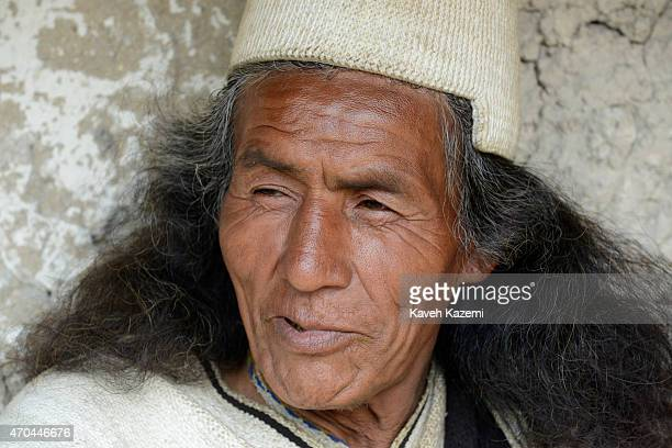A typically dressed Arhuaco man sits outside a hut in the walled village on January 23 2015 in Nabusimake Colombia Nabusimake is the spiritual center...