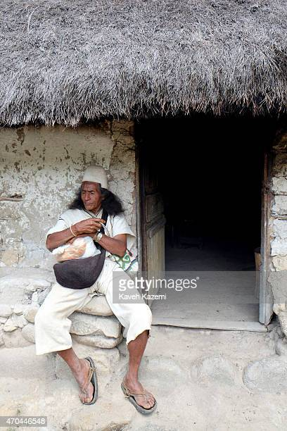 A typically dressed Arhuaco man sits outside a hut inside the walled village on January 23 2015 in Nabusimake Colombia The Arhuaco men appear in...