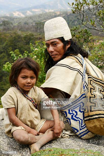 A typically dressed Arhuaco man sits with a young boy on a hill top on January 23 2015 near Nabusimake Colombia The Arhuaco men appear in white...