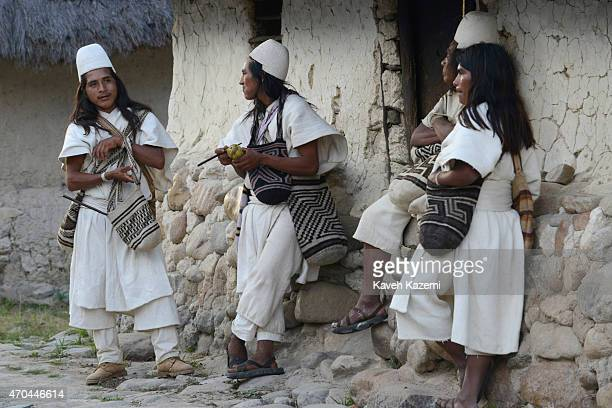 Typically dressed Arhuaco men stand outside a hut in the walled village on January 23 2015 Nabusimake Colombia The Arhuacos appear in white serapes...