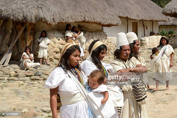 Typically dressed Arhuacos stand inside their walled village on January 23 2015 Nabusimake Colombia The Arhuacos appear in white serapes and carry...
