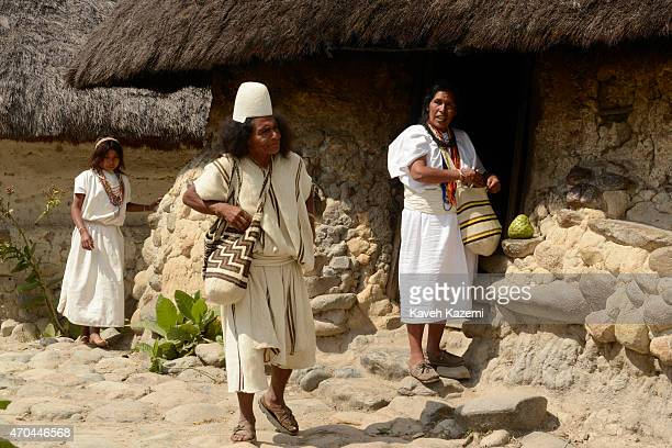 Typically dressed Arhuacos walk inside their walled village on January 23 2015 in Nabusimake Colombia The Arhuaco men appear in white serapes tall...
