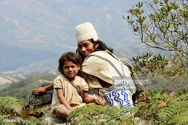 A typically dressed Aruhaco man sits with a young boy on a hill top on January 23 2015 near Nabusimake Colombia The Arhuaco men appear in white...