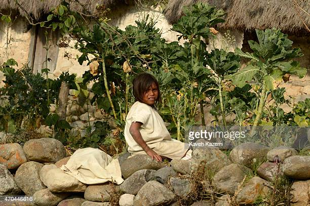 A typically dressed young Arhuaco boy sits on the village wall on January 23 2015 in Nabusimake Colombia The Arhuaco men appear in white serapes tall...