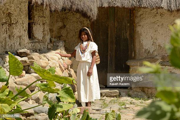 A typically dressed young Arhuaco girl stands in front of a hut inside the walled village on January 23 2015 in Nabusimake Colombia Nabusimake is the...