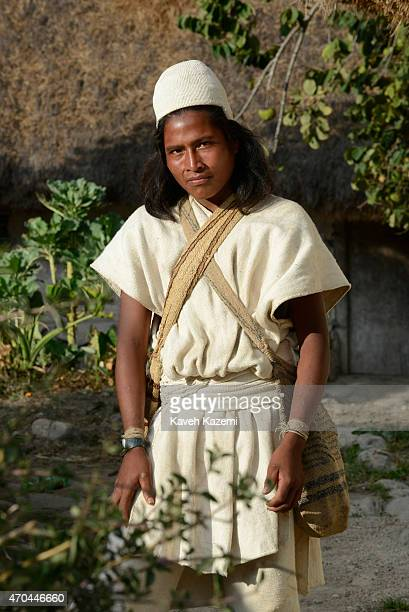 A typically dressed young Arhuaco man stands inside the walled village on January 23 2015 in Nabusimake Colombia The Arhuaco men appear in white...