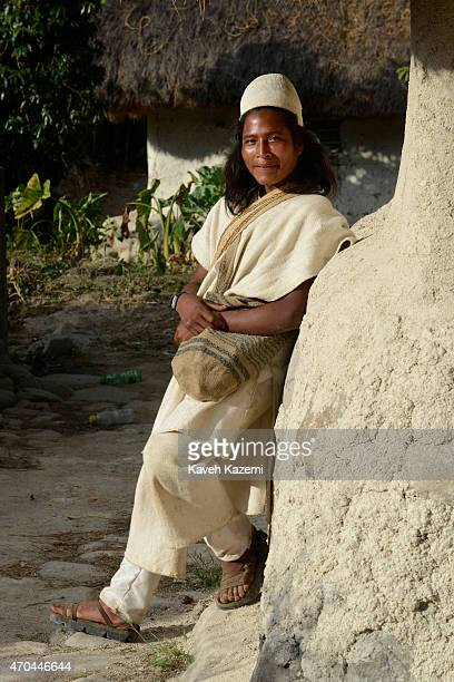 A typically dressed young Arhuaco man stands leaning against a wall inside the village on January 23 2015 in Nabusimake Colombia The Arhuaco men...