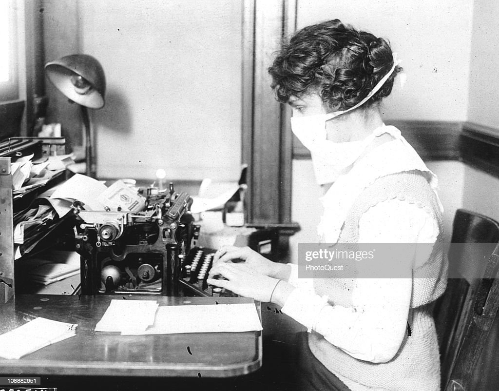 A typist wears mask while working at her office desk during the influenza epidemic 1918