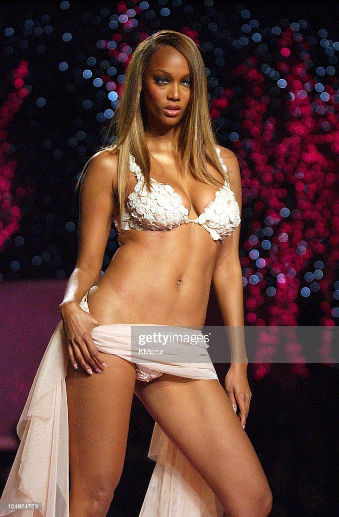 Tyra Banks wearing embellished Victoria's Secret body bare satin DeepV bra and thong tulle micro dress