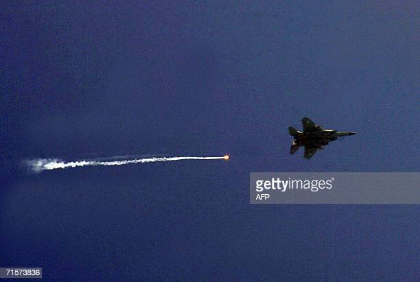 A flare trails behind an Israeli warplane flying over the southern port city of Tyre late 02 August 2006 Israeli forces unleashed fresh air strikes...
