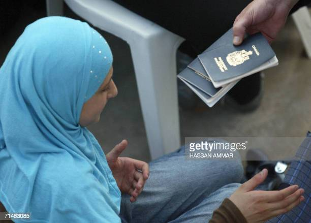 A UN official checks passports of Lebaneseborn Canadian nationals to be evacuated in the southern Lebanese port city of Tyre 19 July 2006 A first...