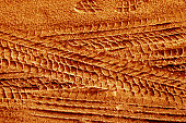 Tyre tracks on sand in orange tone. Abstract background and pattern.