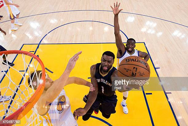 Tyreke Evans of the New Orleans Pelicans goes in for a layup over Draymond Green and Andrew Bogut of the Golden State Warriors in the third second...