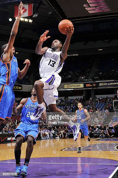 Tyreke Evans of the Sacramento Kings drives to the basket for a layup against Kevin Durant and Jeff Green of the Oklahoma City Thunder during the...