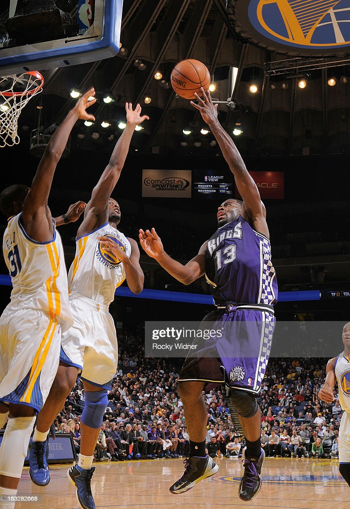 Tyreke Evans #13 of the Sacramento Kings shoots a layup against Harrison Barnes #40 and Festus Ezeli #31 of the Golden State Warriors on March 6, 2013 at Oracle Arena in Oakland, California.