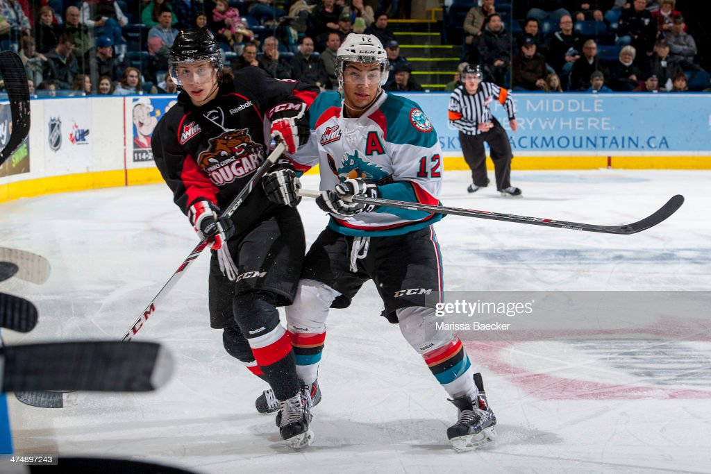 Tyrell Goulbourne #12 of the Kelowna Rockets checks a player of the Prince George Cougars during first period on February 25, 2014 at Prospera Place in Kelowna, British Columbia, Canada.