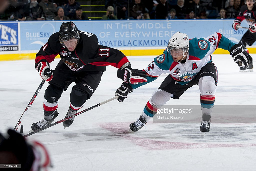 Tyrell Goulbourne #12 of the Kelowna Rockets stick checks Aaron Macklin #11 of the Prince George Cougars during first period on February 25, 2014 at Prospera Place in Kelowna, British Columbia, Canada.
