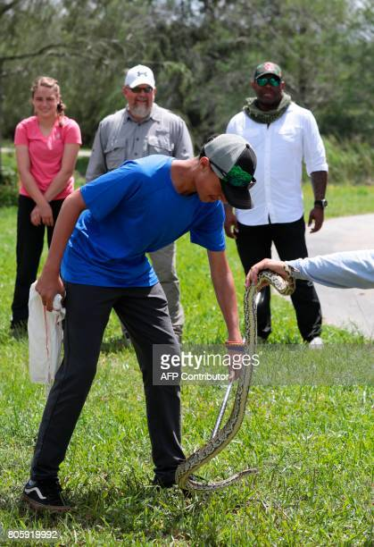 Tyrell Hall and a US Florida Fish and Wildlife Conservation Commission staff holds a burmese python during a training with a Soul River group at the...