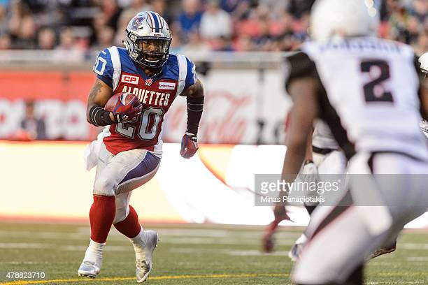 Tyrell Sutton of the Montreal Alouettes runs with the ball during the CFL game against the Ottawa Redblacks at Percival Molson Stadium on June 25...