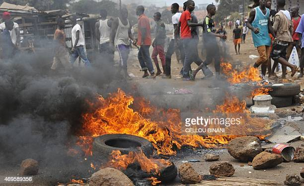 Tyres burn during clash between anti riot policemen and Guinean opposition supporters on April 13 2015 in Conakry Several protesters were wounded on...