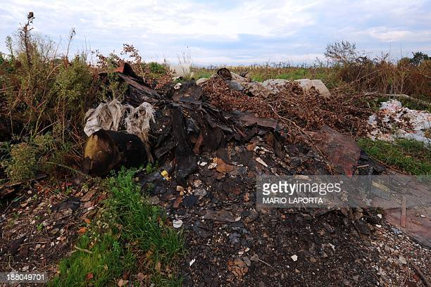 Tyres leather and burnt toxic waste are left strewn on the sides of an agriculture field near Orta di Atella southern Italy on November 14 2013 Orta...