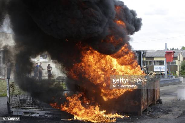Tyres set ablaze by employees in a dumspter burn up in black smoke outside the plant of the GMS company on June 27 2017 in La Souterraine central...