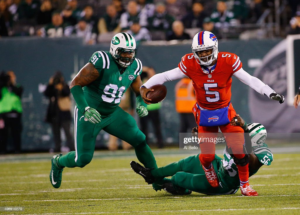 Tyrod Taylor of the Buffalo Bills runs as Demario Davis of the New York Jets attempts the tackle during their game at MetLife Stadium on November 12...
