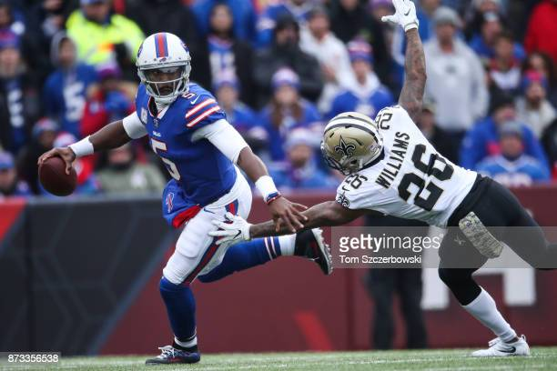 Tyrod Taylor of the Buffalo Bills runs with the ball as PJ Williams of the New Orleans Saints attempts to tackle him during the second quarter on...