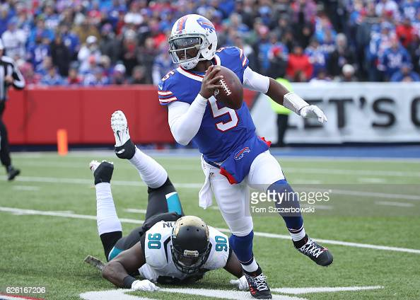 Tyrod Taylor of the Buffalo Bills runs with the ball during NFL game action as Malik Jackson of the Jacksonville Jaguars misses a tackle at New Era...