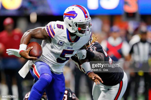 Tyrod Taylor of the Buffalo Bills slips away from Grady Jarrett of the Atlanta Falcons and Takkarist McKinley during the second half at MercedesBenz...