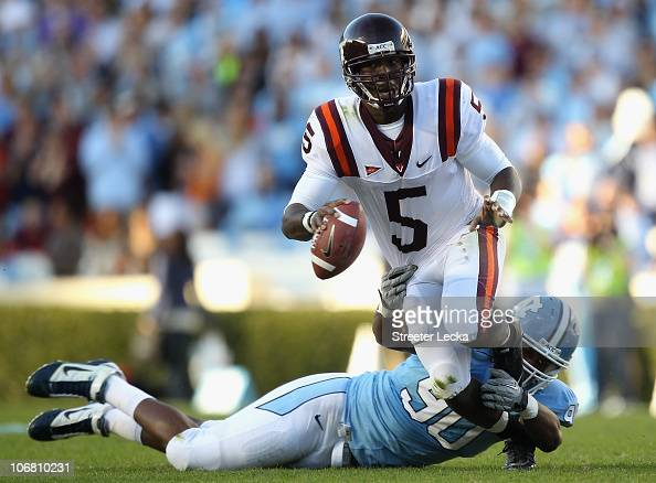 Tyrod Taylor of the Virginia Tech Hokies tries to get away from Quinton Coples of the North Carolina Tar Heels during their game at Kenan Stadium on...