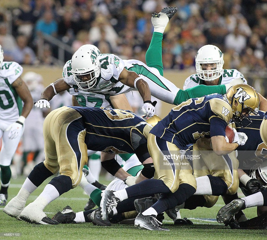 Tyron Brackenridge #41 of the Saskatchewan Roughriders goes airborne as he tries to stop Robert Marve #16 of the Winnipeg Blue Bombers in second-half action in a CFL game at Investors Group Field on August 7, 2014 in Winnipeg, Manitoba, Canada.