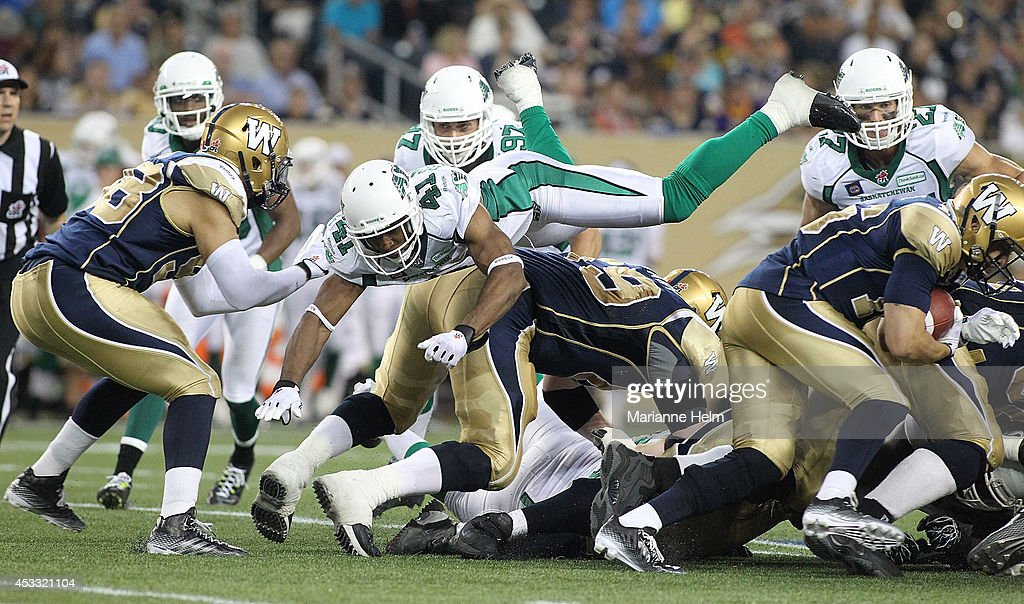 Tyron Brackenridge #41 of the Saskatchewan Roughriders goes airborne in an effort to stop make the stop against Robert Marve #16 of the Winnipeg Blue Bombers in second-half action in a CFL game at Investors Group Field on August 7, 2014 in Winnipeg, Manitoba, Canada.