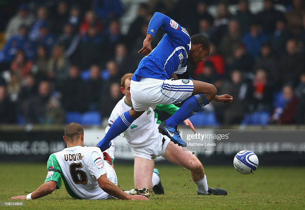 Tyrone Barnett of Macclesfield beats the tackle from Anwar Uddin of Barnet during the npower League Two match between Macclesfield Town and Barnet at the Moss Rose Stadium on January 22, 2011 in Macclesfield, England.