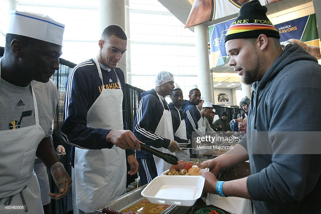 Tyrone Corbin Head Coach and Rudy Gobert #27 of the Utah Jazz dishes out food during the we care-we share Thanksgiving Dinner feeding the homeless at EnergySolutions Arena on November 27, 2013 in Salt Lake City, Utah.