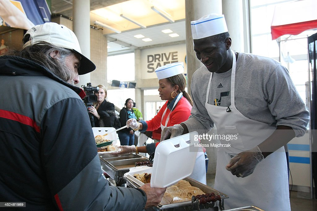 Tyrone Corbin Head Coach of the Utah Jazz dishes out food during the we care-we share Thanksgiving Dinner feeding the homeless at EnergySolutions Arena on November 27, 2013 in Salt Lake City, Utah.